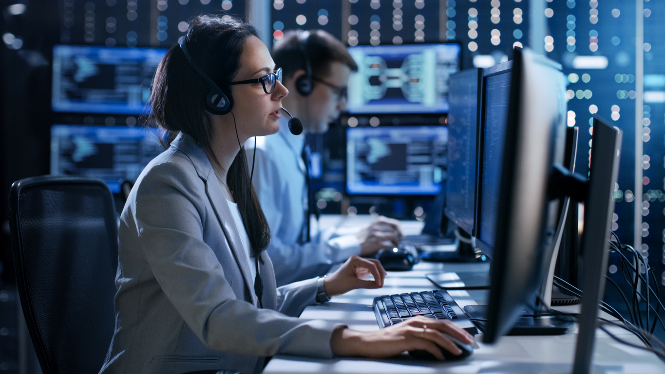 Female working in a Technical Support Team Gives Instructions with the Help of the Headsets. In the Background People Working and Monitors Show Various Information.